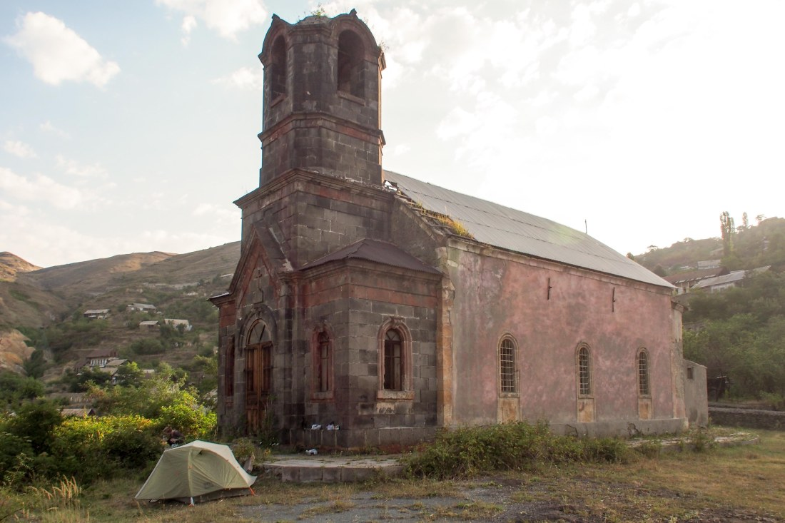 Our tent, parked in front of an abandoned church in an abandoned town.